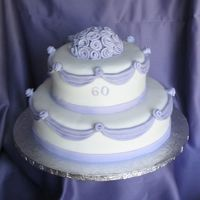 60Th Anniversary Fondant covered with fondant swags and ribbon roses. This is the first traditional shaped cake I ever covered in fondant. There were some...