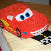 Lightning Mcqueen Cars Cake This is a yellow cake with buttercream frosting. Lightning is piped with red buttercream with fondant accents :o) I carved the shape of the...