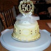 Close Up Of Topper 50Th Anniversary Cake close up of topper 50th anniversary cake. buttercream iceing dusted with shimmer gold dust.