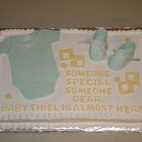 Baby Shower Baby shower cake. Almond sourcream poundcake with buttercream frosting.MMF onesie and gumpaste booties.