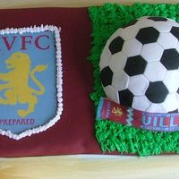 "Football (Soccer) Cake For Hubby 8"" x 16"" x 3"" Chocolate cake covered with Burgundy / claret fondant...Team colours used.... Had to use tulle bow to cover..."