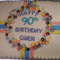 90Th Birthday Buttercream covered cake with fondant ribbons and gumpaste flowers.