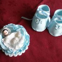 Baby Booties And Baby In A Rose Sugar decorations for the tope of a baby shower or christening cake. Everything from gum paste.