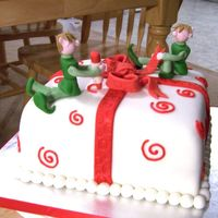 Santa Helpers Chocolate cake covered with white fondant, fondant bow and gumpaste elfs.
