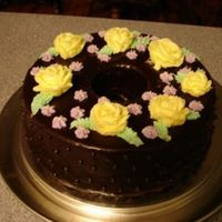 Chocolate Ganache Cake chocolate cake covered in dark chocolate ganache. Decorated with yellow roses we made in 1st Wilton Class.