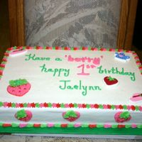 Happy 1St Birthday Jaelynn! Cake is yellow marbeled with buttercream icing. Theme for the party was Strawberry Shortcake. A candle was placed on the cake at the party...