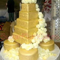 Gold Wedding Cake 5 tiered wedding cake. Top 2 tiers are strawberry with coconut buttercream covered in mmf and airbrushed gold. Bottom 3 tiers are dummy...