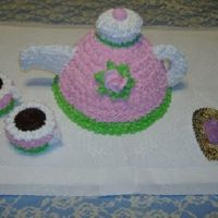 Tea Pot Cake All iced in buttercream. Top of tea pot and tea cups are cupcakes. Molded candy mints on doilie.