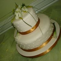 Calla Lilies Top teir is a dummy second tier is a Mocha cake with mocha buttercream filled with ganache. Covered in marzipan and fondant. Fresh calla to...