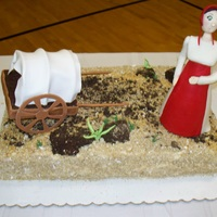 Pioneer Woman Cake Cake ball boulders, shredded wheat dirt, gumpaste figure & wagon. Trying to develop my figure making skills.