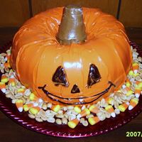 Pumpkin Cake  This is just 2 Bundt Cakes placed on top of each other.... The stem is an ice cream cone covered in chocolate BC and the decorations around...