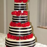 A Formal Cake The cake was designed to match the bridal party. MMF covered with black satin ribbons with fresh roses. 16, 12, 8 & 6 inch tiers.
