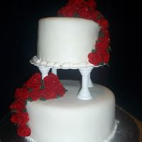 "Two Tier Cake 6x4"" Coconut Cake, 10x4"" White Cake, both with vanilla buttercream. Covered in MMF. Red Fondant Roses"