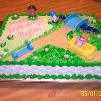 Dora Birthday Cake This cake was made from buttercream. The road was made with crushed graham crackers and the grass was made with the grass tip. My...