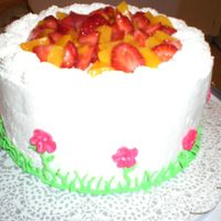 Birthday Cake angel food cake with whipped icing, strawberries and peaches in the middles and on top.