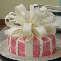 Pink Gift Simple round cake, covered in fondant. Bow done in fondant, too. Cake painted with pink luster dust.