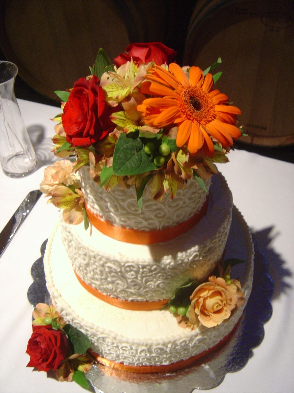 Beautiful Fall Wedding! Ivory buttercream frosting with orange ribbon and various flowers.