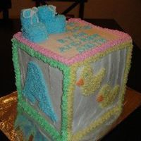 "Baby Block Cake Made with layered 8"" square. All done in buttercream. Booties on top are decorated marshmallows."