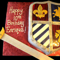 Medieval Shield Cake Sword made of pastillage with a sugar jewel. All decorations were sculpted with fondant and painted with gold luster dust. The cross has a...