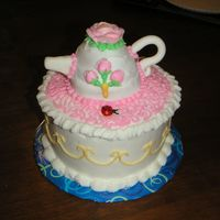 Picture_089.jpg My very first tea pot cake. Cake is white and tea pot is lemon. Everything's buttercream except fondant handle and spout.