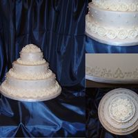 Ring Of Roses The cake is iced in Ivory buttercream and the roses are make out of royal. I covered the board with fondant and then embossed a delicate...