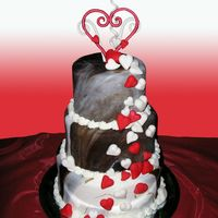 Cascading Hearts This cake is chocolate and white marbeled fondant. The hearts are fondant and the topper is gumpaste. Its chocolate and white cake in...