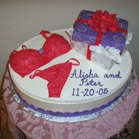 Lingerie Shower Cake This cake is chocolate kahlua mousse, yummy. The bra and panties and bow are gumpaste painted with red petal dust. The gift is fondant...