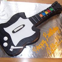 Coltons Guitar Hero Cake This was for my cousins 12th birthday. its one layer chocolate, carved in the shape of a guitar hero guitar. its based iced in chocoate...