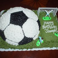 "Soccer Cake Chocolate soccer cake over a chocolate cookie covered in ""grass"" icing."
