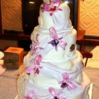My Wedding Cake Fondant covered, four tier, two layers each, fondant orchids, chocolate shells, dolphin topper. Took about five days all together.