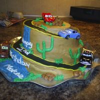 "Disney Cars Cake This cake was for a 2 year old boy. The mountain is carved from a 10"" and 8"" cake. WASC cake, all bc decorations. I bought the..."
