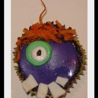One-Eyed Purple People Eater cupcake with fondant decoration. 'hair' is coconut dyed orange