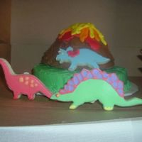 Volcano Cake With Dinosaur Cookies A volcano cake with dinosaur cookies.