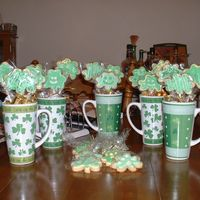 St. Patty's Day Cookie Bouquet Caramel sugar cookies with royal icing. The mugs are also filled with gold and silver nuggets.
