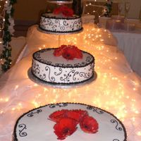 Red, Black, And White Wedding Cake The bride wanted black scrolls. The red came from the live daisies.