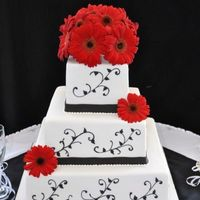Black, White, And Red did this one in fondant with just a simple black royal icing leaf and scroll look on each tier. Live gerbera daises. I loved how the red...