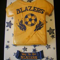 Blazers Soccer Cake carved from a double stacked sheet cake, fondant covered, airbrushed and freehanded the logo by cutting it out of blue fondant, TFL!