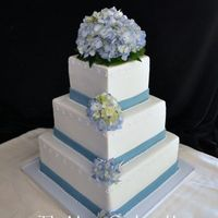 Hydrangea Wedd cake done in fond. with royal icing wave pattern and fond. bands, live hydrangea were put on top and down the sides to give it a different...