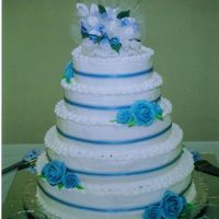 Blue Love  My first wedding cake. 5 tiers, buttercream icing with blue royal icing roses. A blue sheer ribbon is in the middle of each tier. Each...