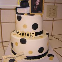 Graduation Black And Gold Two Tier Graduation Cake with black and gold accents and book.
