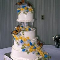 Butterfly Cake yellow gumpaste roses with blue accents. I cheated and used purchased butterflies Buttercream frosting with bead border.