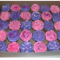 Birthday Cupcakes vanilla cupcakes with pink and purple buttercream with a variety of sprinkles