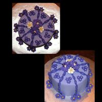 Purple_Cake_003_Copy.jpg This is my first fondant covered cake. I did it in class. Two tones of purple fondant, with royal icing flowers. If it happens to look blue...