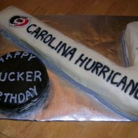 Carolina Hurricanes Hockey Stick And Puck White cake with BC icing and accents. Chocolate cake puck with chocolate icing dyed black. TFL