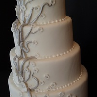 Silver & White 4-tier round cake with silver branches & white flowers with silver pearl centers. Very simple.