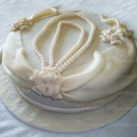 "White Pearls 12"" round chocolate cake with chocolate filling, covered in fondant. The pearls are made of fondant. The drapes and flowers are made..."