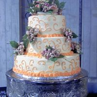 Ivory And Peach Wedding Cake  3 tier buttercream torted with homemade strawberry filling. The flowers on the cake were provided and I thought they really didn't...