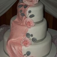 Pink And White Vanilla sponge cake covered in fondant. fondant drape and gumpaste roses