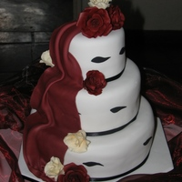 Burgandy Roses vanilla sponge cake covered in fondant with fondant drape. Gumpaste roses