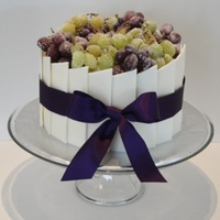 Chocolate And Sugared Grapes A regular buttercream cake covered in white chocolate panels (I hand cut each one) and topped with sugared grapes. Tied with a fabric...